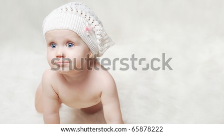 Smiling little baby on a soft blanket with hat - stock photo