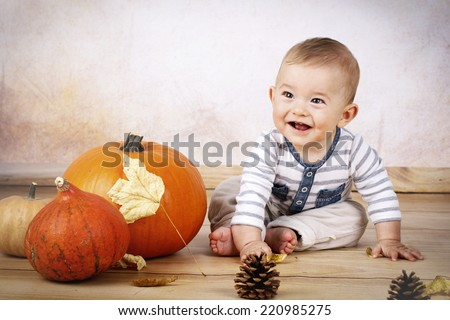 Smiling little baby sitting with pumpkins  - stock photo