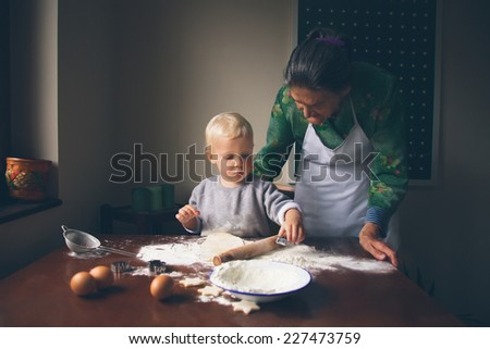 Smiling little baker knead Christmas cookies. - stock photo