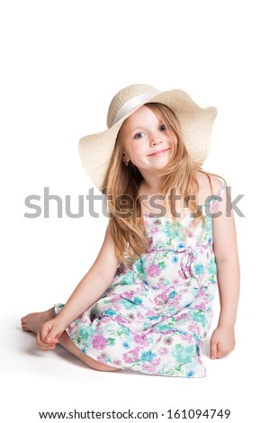 smiling little blonde girl wearing big white hat and dress  sitting on the floor over white background  - stock photo