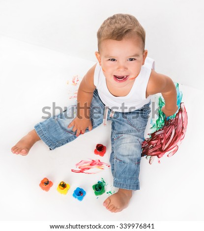 smiling little boy and gouache above photo on white background - stock photo