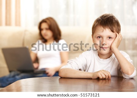 smiling little boy and mother with laptop on background