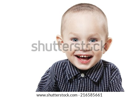 Smiling  little boy at the age of two in a shirt and jeans on white background playing cubes looking at the camera
