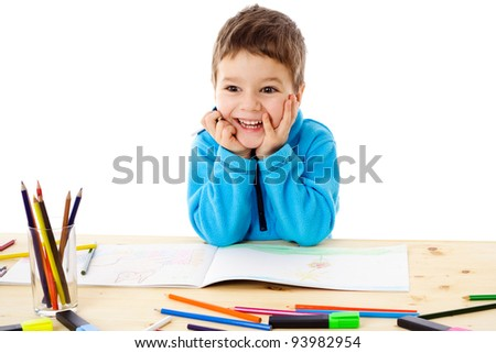 Smiling little boy at the table draw with crayons, isolated on white
