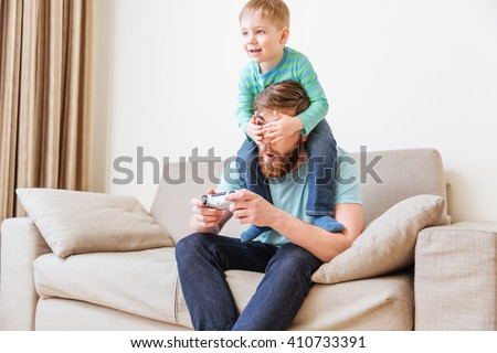 Smiling little boy covering eyes of his father while he playing computer games on sofa at home  - stock photo