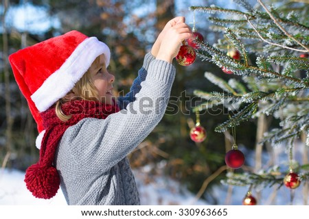 Smiling little boy decorates Christmas tree in winter forest - stock photo
