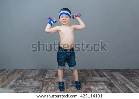 Smiling little boy doing exercises with dumbbells over grey background - stock photo