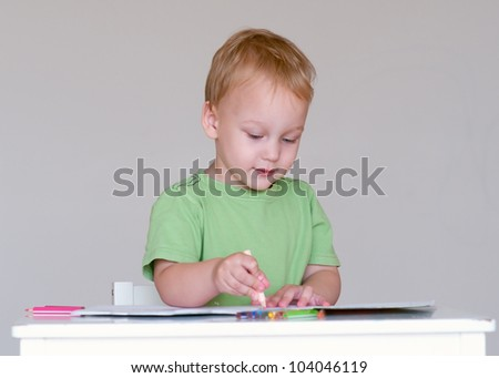 Smiling little boy drawing