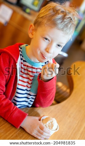 smiling little boy eating his ice-cream in cafe - stock photo