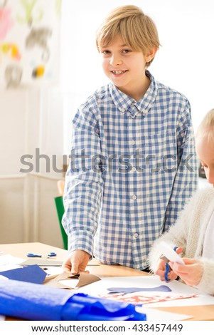 Smiling little boy having fun during art classes. Sitting next to his friend and drawing the picture