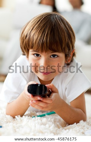 Smiling little boy holding a remote lying on the floor in the living-room - stock photo