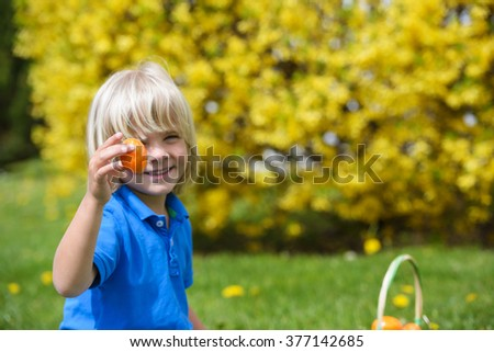 Smiling  little boy  holding colored Easter egg in hand outdoors - stock photo