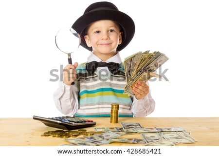 Smiling little boy in black hat counting money on the table, isolated on white - stock photo