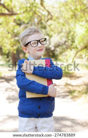 smiling little boy in glasses holding book, back to school concept - stock photo