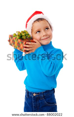 Smiling little boy in Santa's hat listen the gift box, isolated on white - stock photo