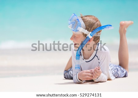 smiling little boy in snorkeling set lying at the beach and enjoying summer vacation at perfect caribbean beach at anguilla island