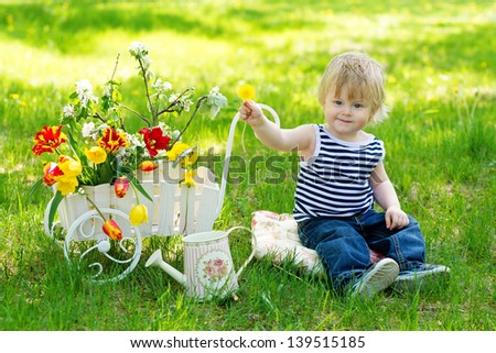 Smiling little boy in striped sleeveless sport shirt sitting on the fresh green grass near decorative wooden wheelbarrow full of flowers
