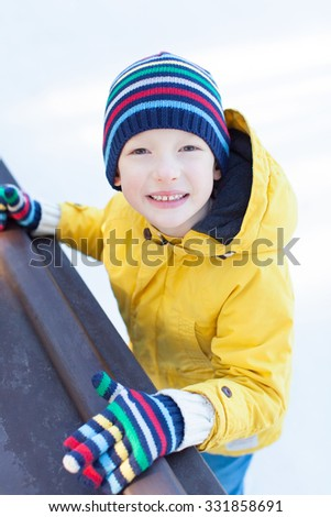 smiling little boy in warm clothes ice skating at outdoor skating rink at winter - stock photo