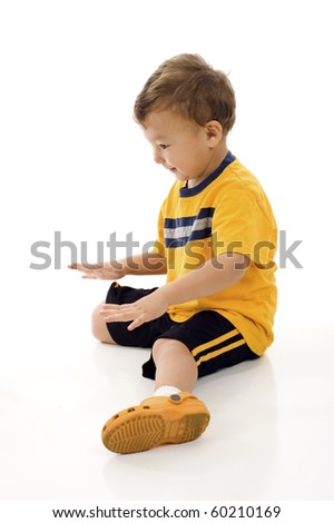 Smiling little boy looking down and touching imaginary product isolated over white background - stock photo