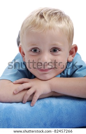 smiling little boy lying down on a blue cushion - stock photo