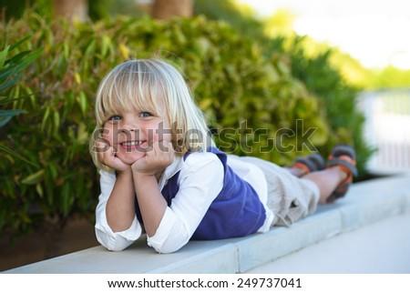 Smiling little boy lying in summer park  - stock photo