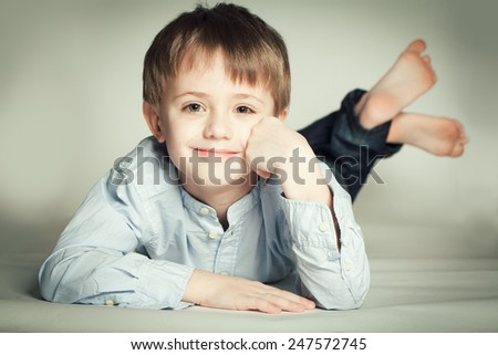 Smiling little boy lying on the floor - stock photo