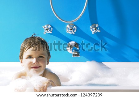 Smiling little boy peeking over the top of a frothy bubble bath against a blue wall - stock photo