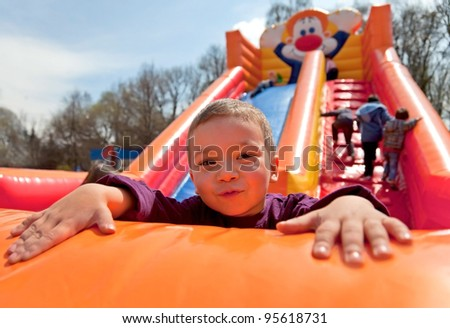 Smiling little boy playing on inflatable slide, looking at camera - stock photo