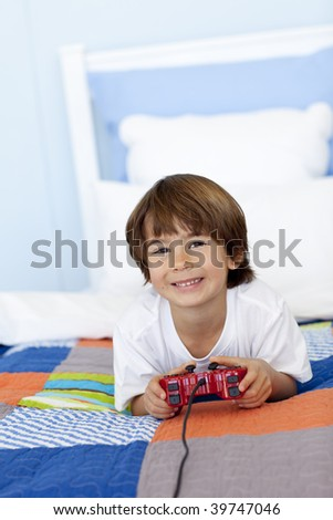 Smiling little boy playing videogames in his bedroom - stock photo