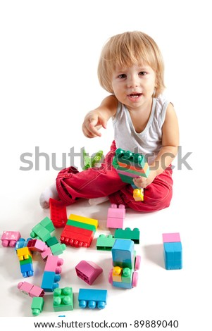 Smiling little boy playing with blocks, isolated on white background - stock photo