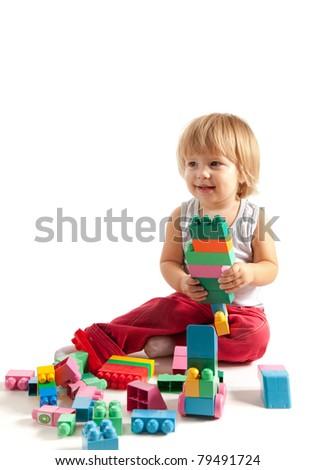 Smiling little boy playing with blocks, studio shot - stock photo