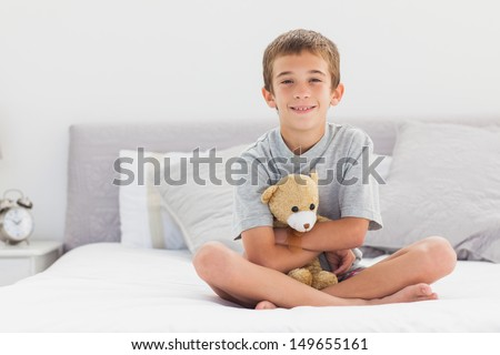 Smiling little boy sitting on bed holding his teddy bear at home - stock photo