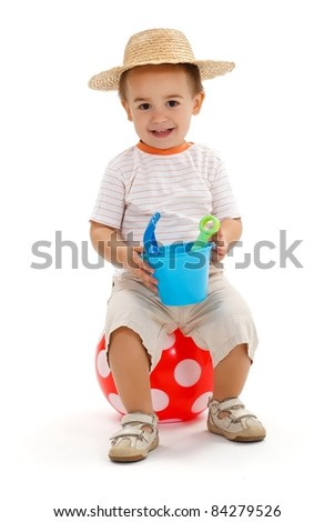Smiling little boy sitting on big, red dotted ball, holding sandbox toys