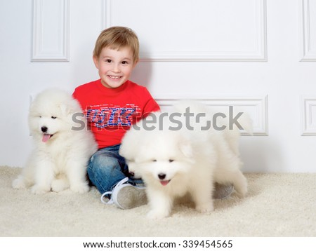 smiling little boy three years old playing with white puppies of Samoyed in studio