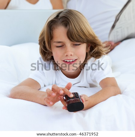 Smiling little boy watching TV lying on the bed - stock photo