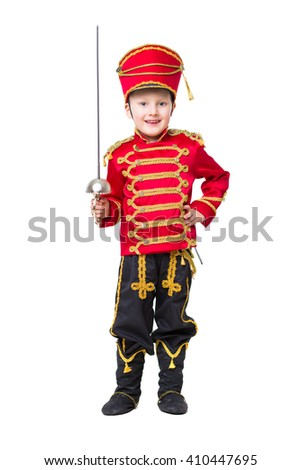 Smiling little boy wearing like guardsman posing with a sword. Isolated on white