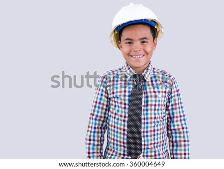 Smiling little boy wearing white hard hat and necktie with checkered shirt on gray background - stock photo