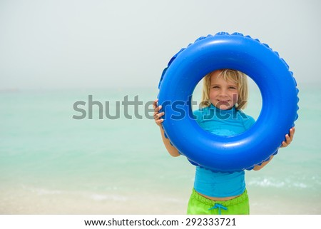 Smiling little boy with a floating ring at a tropical beach - stock photo