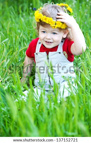 Smiling little boy with a wreath of dandelions in park - stock photo