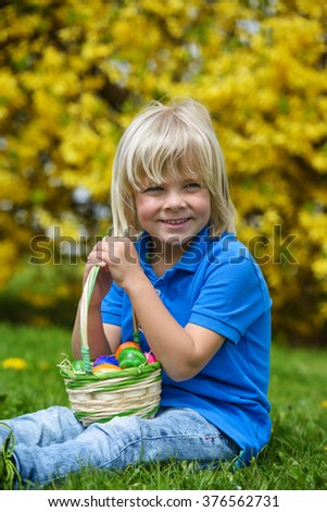 Smiling  little boy with basket full of colorful easter eggs outdoors - stock photo