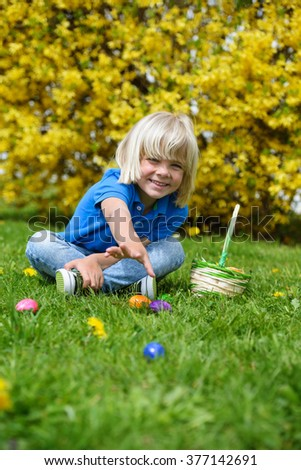 Smiling little boy with basket  looking Easter eggs outdoors on a sunny day  - stock photo