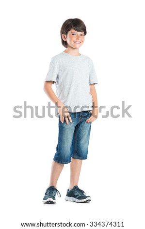 Smiling little boy with freckles standing isolated on white background. Portrait of satisfied cute child in casual clothes looking at camera with hand in pocket standing against white background.  - stock photo