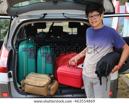 smiling little boy with glasses loaded the trunk of the car before leaving with family