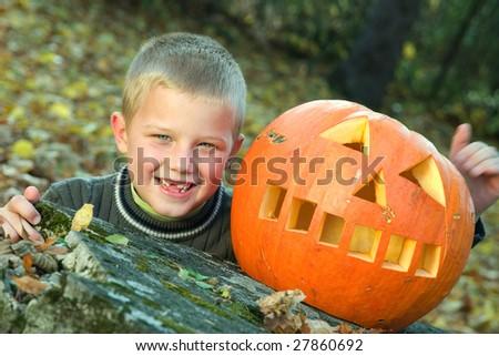 Smiling little boy with halloween pumpkin - stock photo