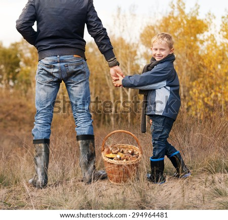Smiling little boy with his father on the mushrooms picking - stock photo