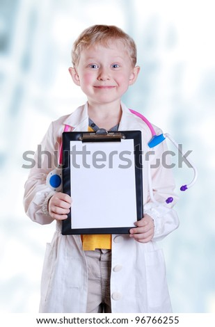 Smiling little boy with medical tools on light blue background - stock photo
