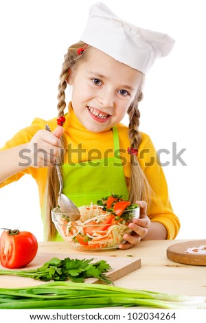 Smiling little chef mix the salad, isolated on white