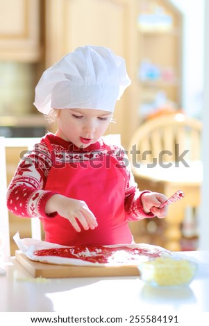 Smiling little child, adorable toddler girl wearing red chef apron and white hat, preparing delicious pizza for family party topping it with tomato sauce, vegetables and cheese, sitting at sunny room - stock photo