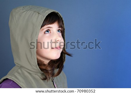 Smiling little child looking up at copyspace isolated on blue background - stock photo