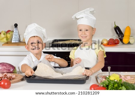 Smiling little cooks in white chefs uniforms preparing a homemade pizza for their lunch placing the rolled dough onto a baking sheet ready for the topping - stock photo